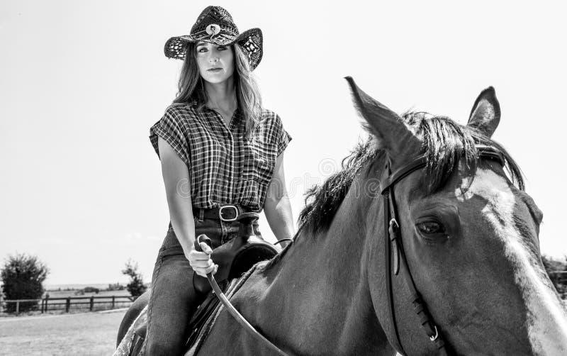 Пастушка смотря камеру пока верховая лошадь с западными седловиной и шляпой стоковое изображение