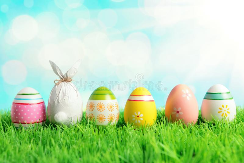 Пасхальное яйцо в оболочке в бумаге в форме зайчика с красочными пасхальными яйцами на зеленой траве Концепция праздников весны стоковые фото