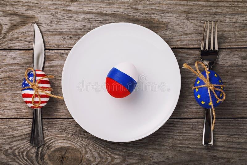 Пасхальное яйцо покрашенное в цвете флага России в белой плите на деревянном столе, взгляд сверху стоковые фото