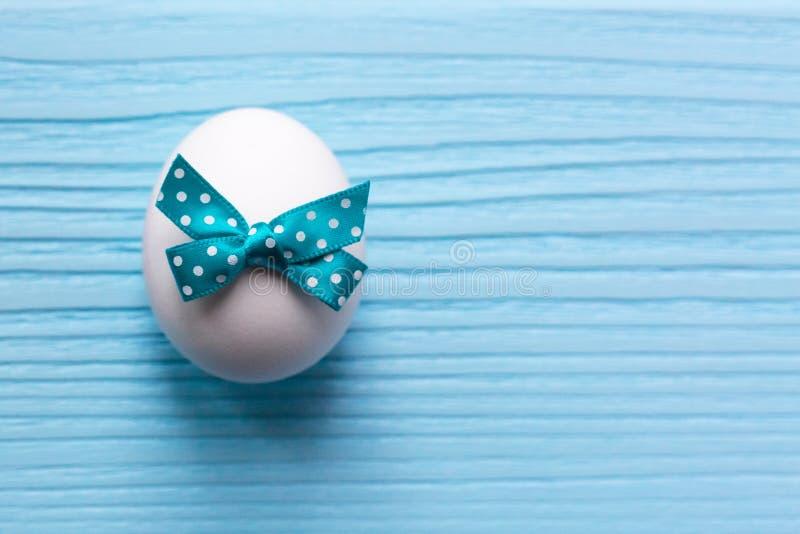 Пасхальное яйцо с белизной запятнало смычок на предпосылке покрашенной синью деревянной стоковые изображения rf