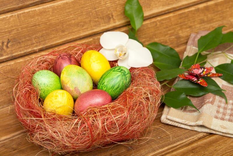 Пасхальные яйца в гнезде и зеленой хворостине с бабочкой на деревянной предпосылке Eggs handmade новый стиль расцветки Концепция  стоковые фото