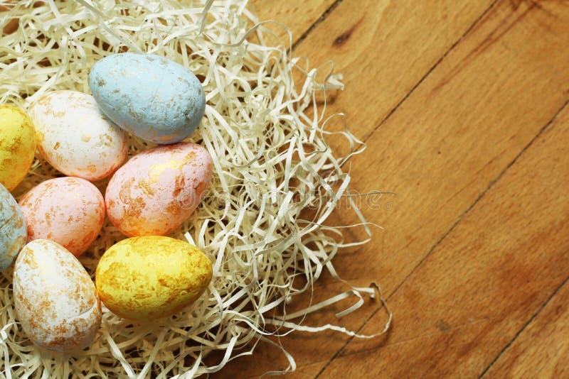 Пасхальные яйца в гнезде на деревянной предпосылке стоковое фото