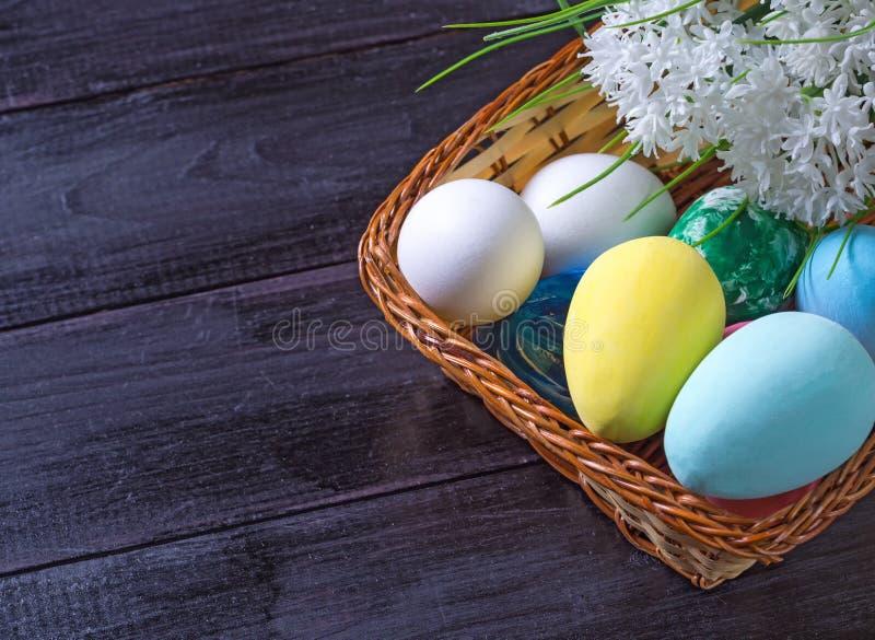 Пасхальные яйца в корзине и белые цветки в темной деревянной предпосылке стоковая фотография