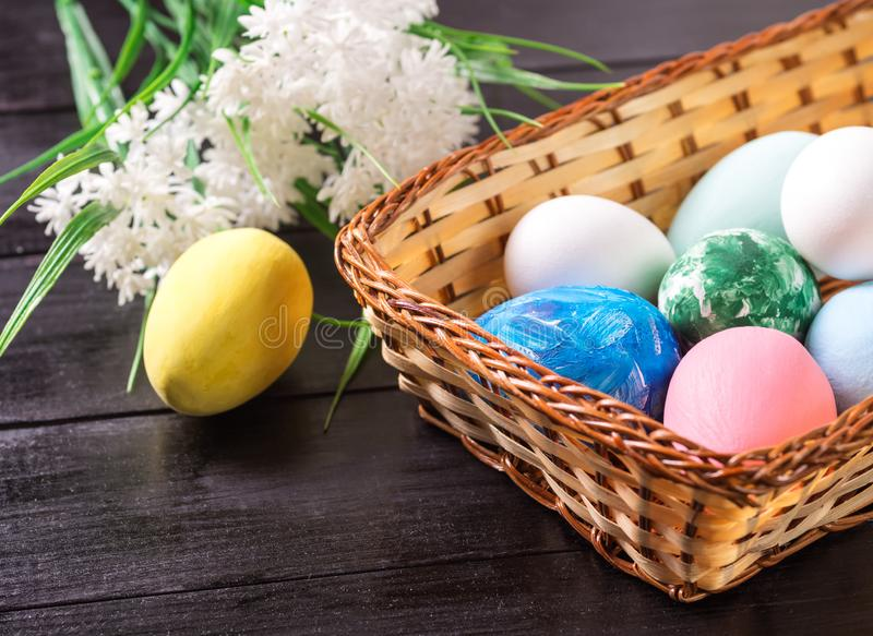 Пасхальные яйца в корзине и белые цветки в темной деревянной предпосылке стоковое изображение
