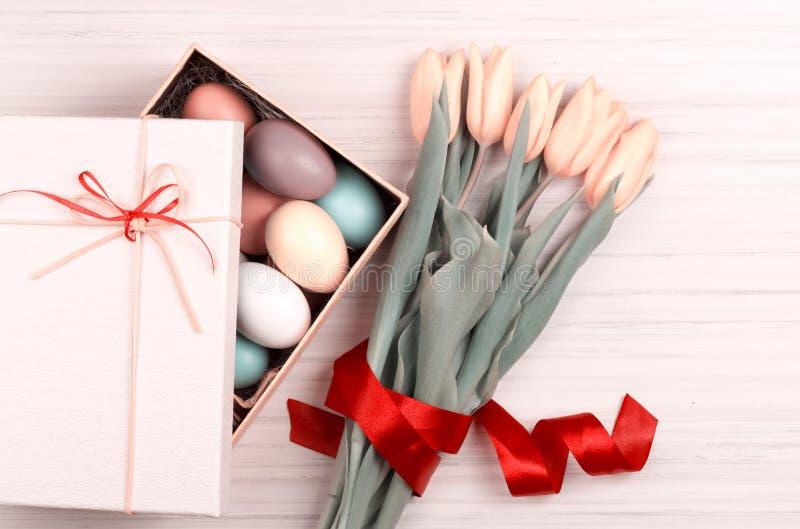 Пасхальные яйца в коробке с красочными желтыми тюльпанами стоковое фото rf