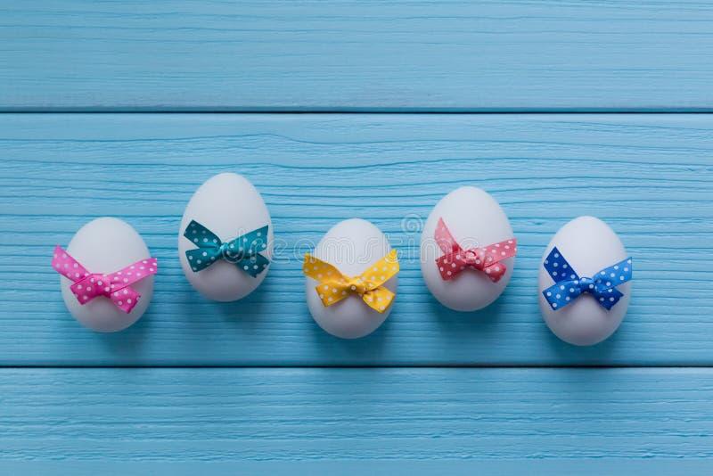 Пасхальные яйца с цветом запятнали малые смычки на предпосылке покрашенной синью деревянной стоковое фото rf