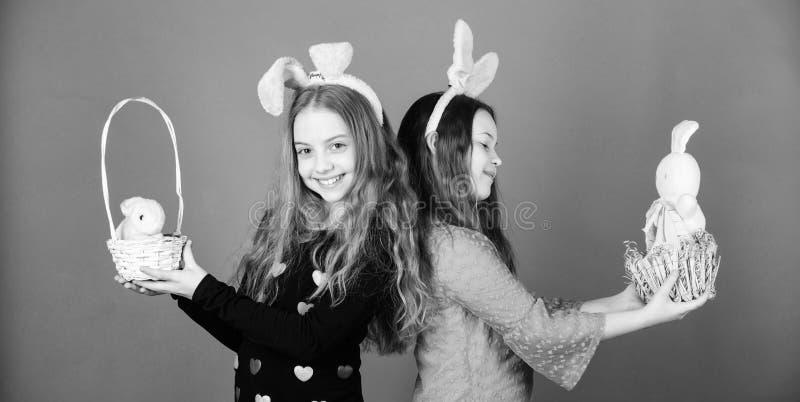 Пасха говорит вне красоту по буквам Дети держа любимцев зайчика в корзинах пасхи Маленькие девочки нося уши зайчика на день пасхи стоковое фото