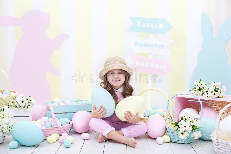 Пасха! девушка держит большие пестротканые яйца в ее руках на фоне интерьера пасхи Милый младенец гонит Easte стоковое фото rf