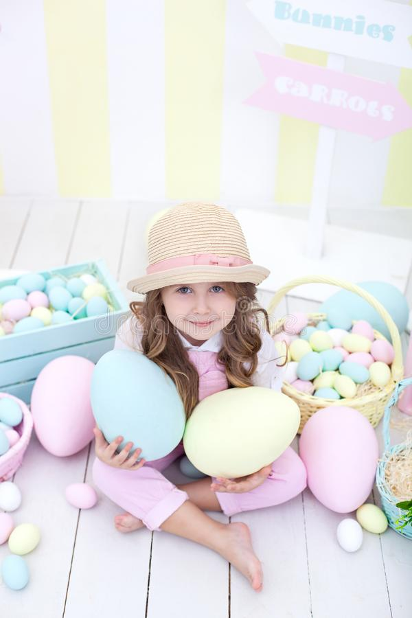 Пасха! девушка держит большие пестротканые яйца в ее руках на фоне интерьера пасхи Милый младенец гонит Easte стоковая фотография rf