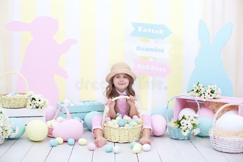 Пасха! Девушка держит корзину яя на предпосылке интерьера пасхи Оформление пасхи красочное Девушка гоня пасхальные яйца Sprin стоковые изображения
