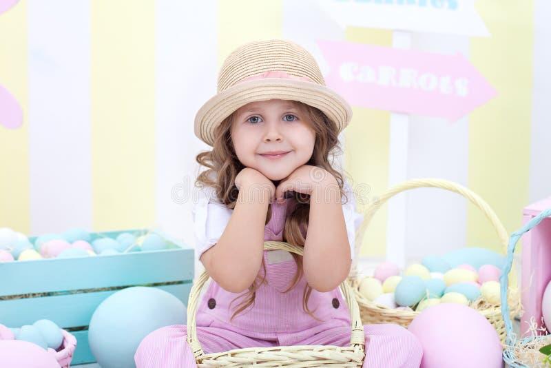Пасха! Девушка держит корзину яя на предпосылке интерьера пасхи Оформление пасхи красочное Девушка гоня пасхальные яйца Sprin стоковое фото rf