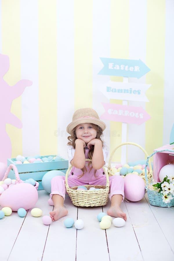 Пасха! Девушка держит корзину яя на предпосылке интерьера пасхи Оформление пасхи красочное в студии Девушка гоня восток стоковая фотография