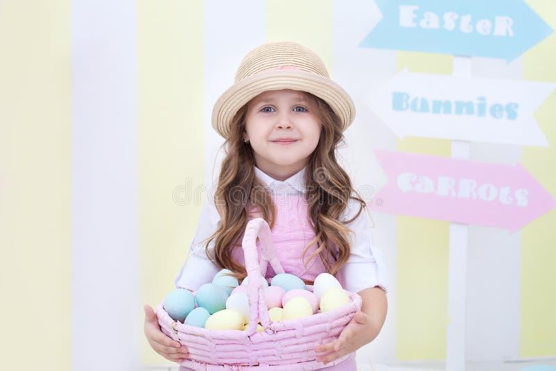 Пасха! Девушка держит корзину яя на фоне интерьера пасхи Оформление пасхи красочное в студии Девушка i стоковые изображения rf