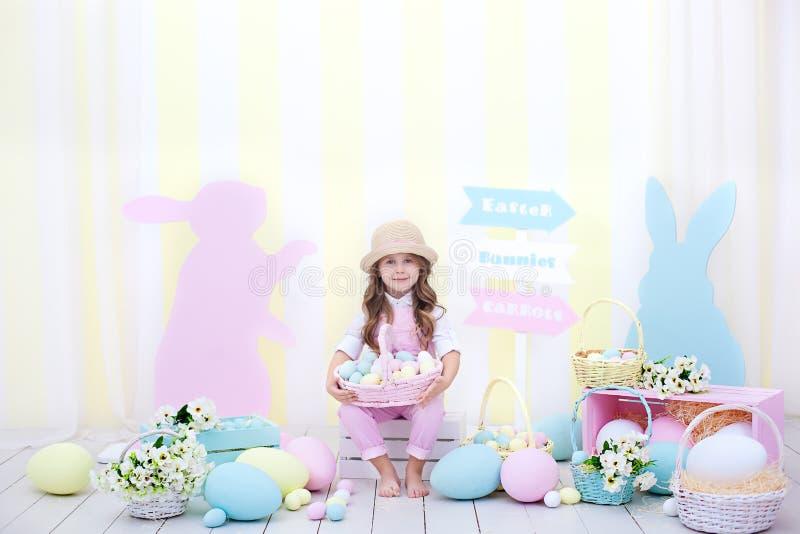 Пасха! Девушка держит корзину яя на фоне интерьера пасхи Оформление пасхи красочное в студии Девушка i стоковые изображения