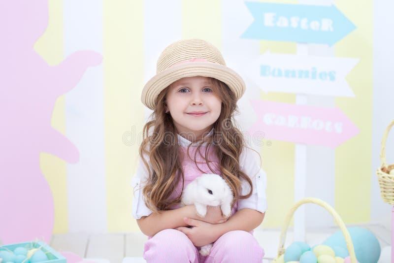 Пасха! Девушка играет с зайчиком пасхи Ребенок держит кролика в его оружиях на фоне интерьера пасхи стоковое изображение