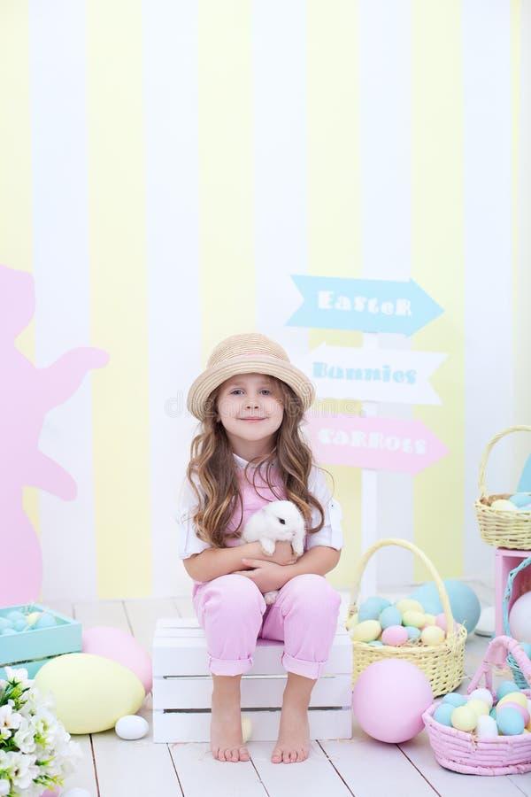 Пасха! Девушка играет с зайчиком пасхи Ребенок держит кролика в его оружиях на фоне интерьера пасхи стоковое изображение rf