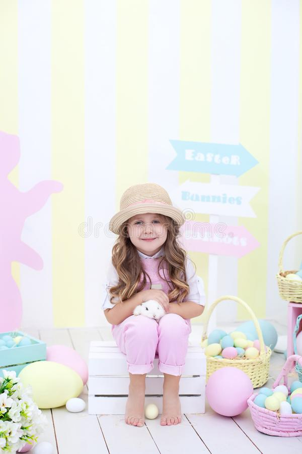 Пасха! Девушка играет с зайчиком пасхи Ребенок держит кролика в его оружиях на фоне интерьера пасхи стоковые фотографии rf