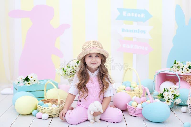 Пасха! Девушка играет с зайчиком пасхи Ребенок держит кролика в его оружиях на фоне интерьера пасхи стоковая фотография rf