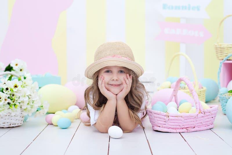 Пасха! девушка на предпосылке интерьера пасхи Оформление пасхи красочное в студии Девушка около корзины с покрашенный стоковое изображение rf
