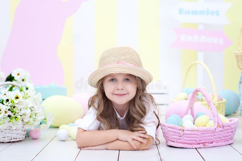 Пасха! девушка на предпосылке интерьера пасхи Оформление пасхи красочное в студии Девушка около корзины с покрашенный стоковое фото