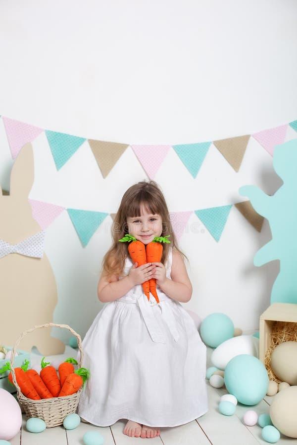 Пасха! Красивая маленькая девочка в белом платье сидя с зайчиками и морковами пасхи Кролик, красочные яйца Много различное colorf стоковые изображения rf