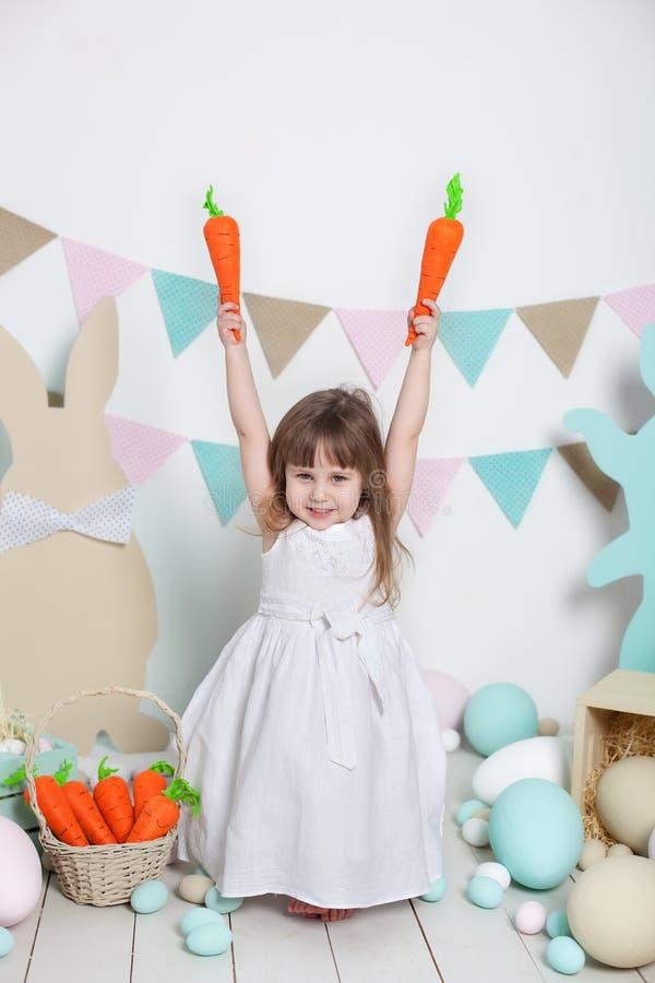 Пасха! Красивая маленькая девочка в белом платье сидя с зайчиками и морковами пасхи Кролик и красочные яйца Много различных co стоковое фото