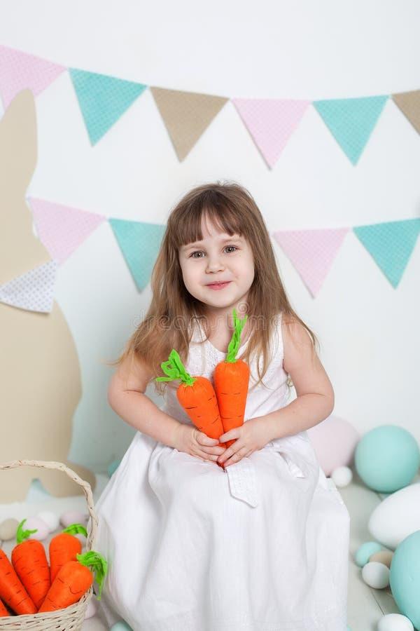 Пасха! Красивая маленькая девочка в белом платье сидя с зайчиками и морковами пасхи Кролик и красочные яйца Много различный col стоковая фотография