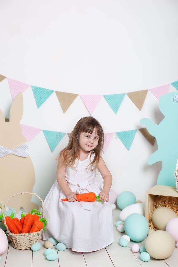 Пасха! Красивая маленькая девочка в белом платье сидя с зайчиками и морковами пасхи Кролик и красочные яйца Много различный col стоковые фото