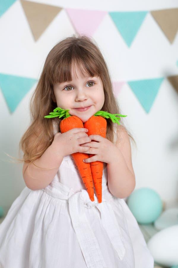 Пасха! Красивая маленькая девочка в белом платье сидя с зайчиками и морковами пасхи Много различных красочных пасхальных яя, colo стоковые изображения