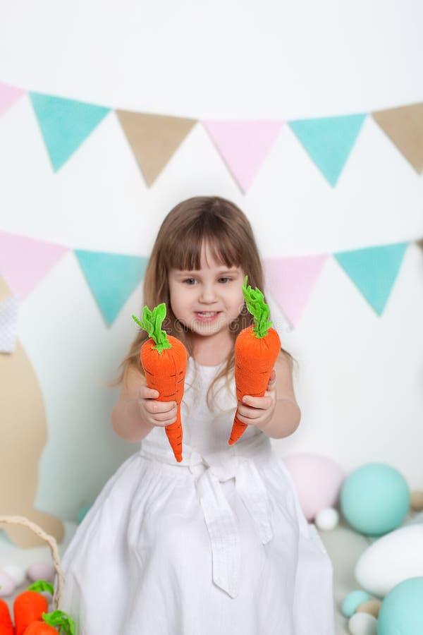 Пасха! Красивая маленькая девочка в белом платье сидя с зайчиками пасхи, морковами Кролик, красочные яйца Много различных красочн стоковая фотография rf
