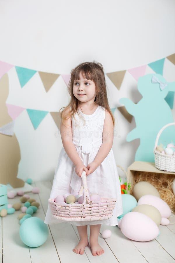 Пасха! Красивая маленькая девочка в белом платье стоит с корзиной пасхи Много различных красочных пасхальных яя, красочных внутри стоковая фотография rf