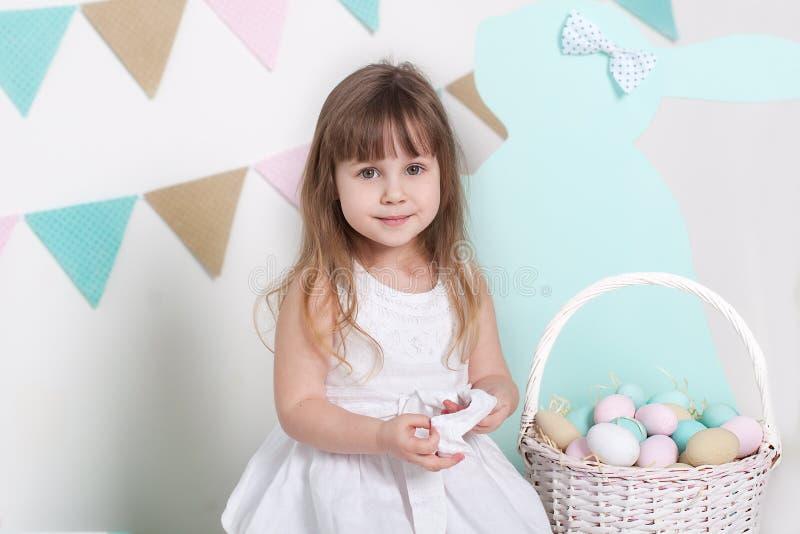 Пасха! Красивая маленькая девочка в белом платье с пасхальными яйцами и корзина на ярком пейзаже пасхи Положение пасхи, decorati стоковое изображение