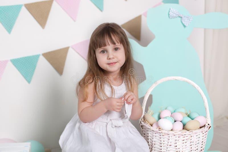 Пасха! Красивая маленькая девочка в белом платье с пасхальными яйцами и корзина на ярком пейзаже пасхи Положение пасхи, decorati стоковые фото