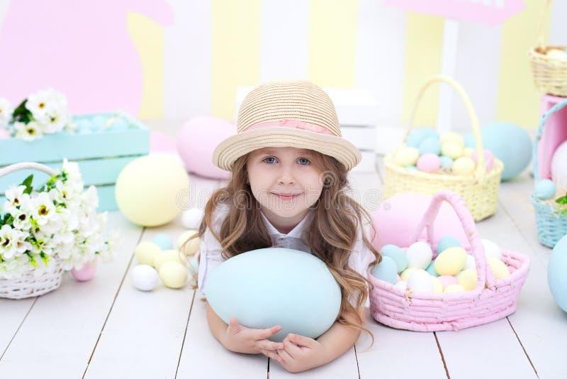 Пасха! Милая девушка играя с пасхальным яйцом Ребенок держит большое красочное яйцо на предпосылке интерьера пасхи Colorfu пасхи стоковые изображения