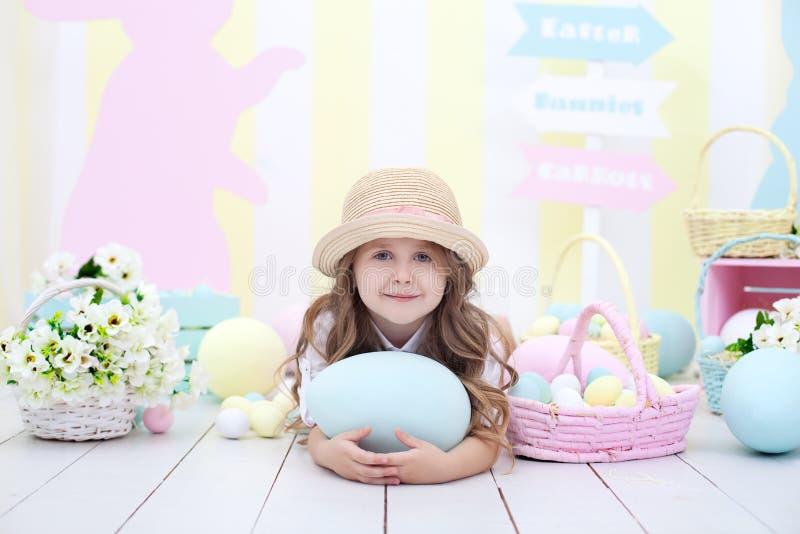 Пасха! Милая девушка играя с пасхальным яйцом Ребенок держит большое красочное яйцо на предпосылке интерьера пасхи Colorfu пасхи стоковое изображение rf