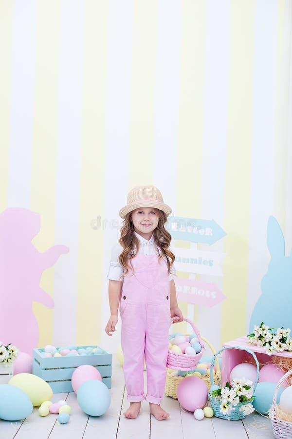 Пасха! Милая девушка стоящ и держащ корзина с яйцами в ее руках с украшением на заднем плане Милая девушка охотится f стоковые фото