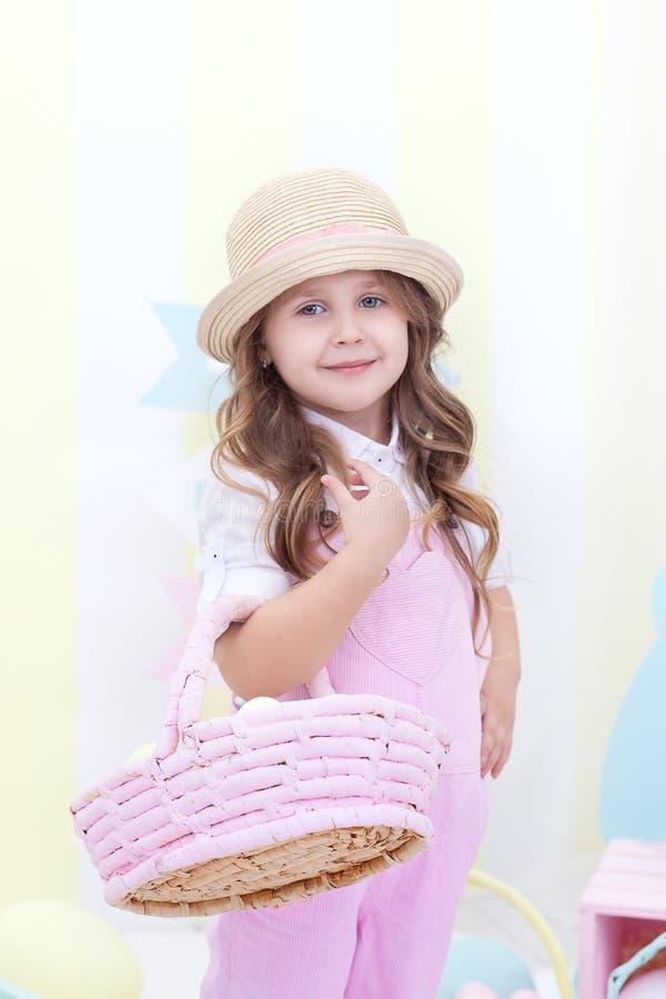 Пасха! Милая девушка стоящ и держащ корзина с яйцами в ее руках с украшением на заднем плане Милая девушка охотится f стоковое фото
