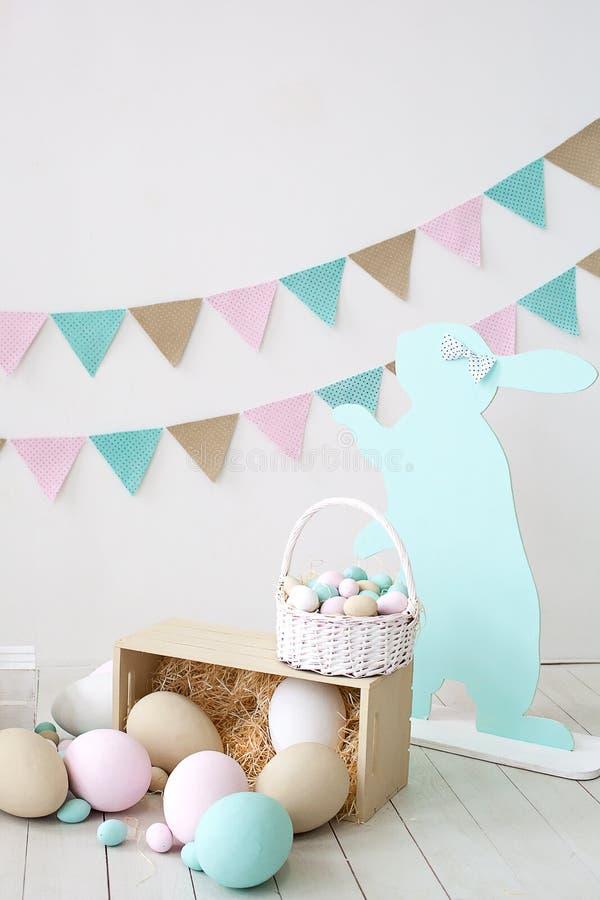 Пасха! Много красочных пасхальных яя с зайчиками и корзинами! Украшение комнаты, комната пасхи детей для игр Корзина с стоковые изображения