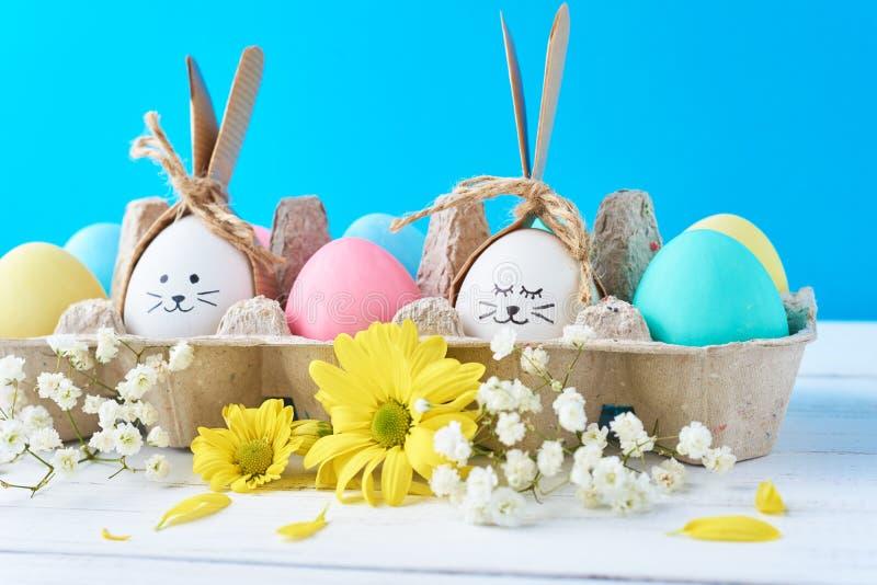Пасха покрасила яйца в бумажном подносе с decorationd на голубой предпосылке стоковые фото