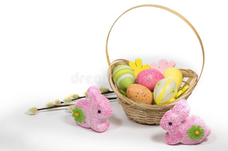 Пасха покрасила яйца в корзине и зайчиках пасхи розовых стоковое фото rf