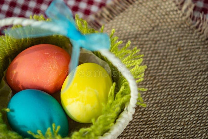 Пасха покрасила яйца в корзине на салфетке холста и checkered скатерти стоковое фото