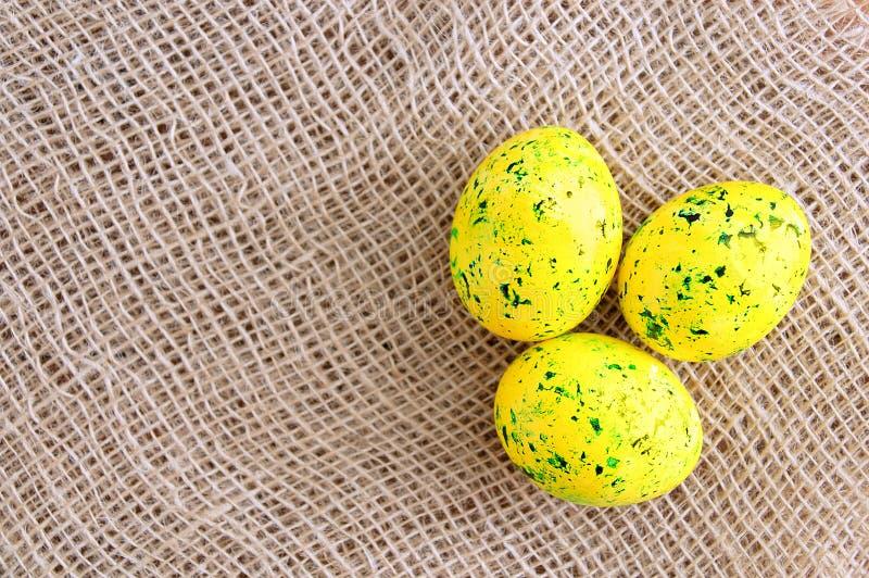 Пасха покрасила яйца желтый с зеленым цветом брызгает На ткани белья коричневой стоковые изображения rf