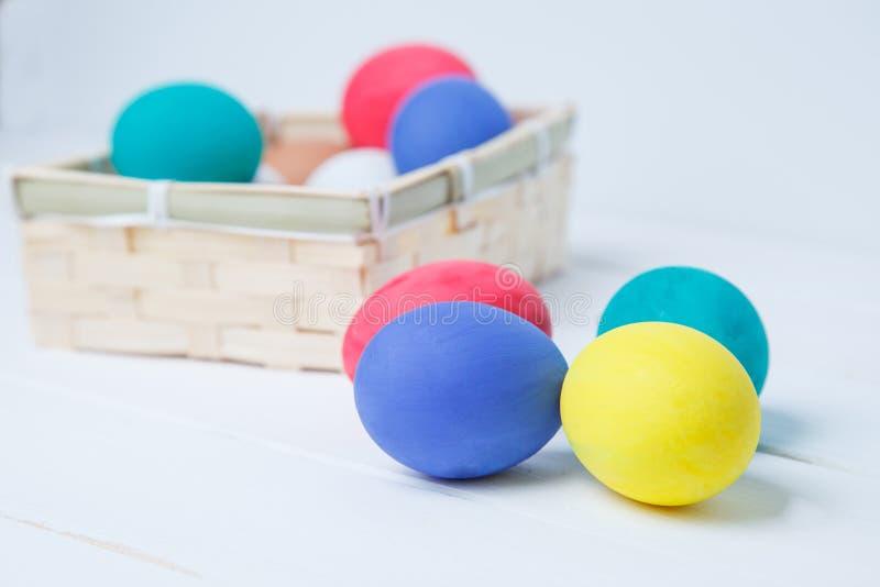 Пасха, праздники, традиция и концепция объекта - близкая вверх покрашенных пасхальных яя в корзине стоковые изображения