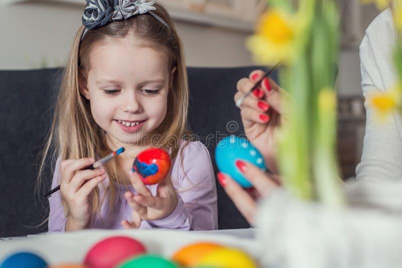 Пасха, семья, праздник и концепция ребенка - близкая вверх яичек расцветки маленькой девочки и матери для пасхи стоковая фотография
