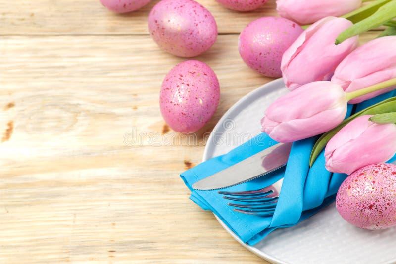 Пасха Сервировка стола пасхи Розовые пасхальные яйца и тюльпаны цветков на естественном деревянном столе пасха счастливая праздни стоковое изображение