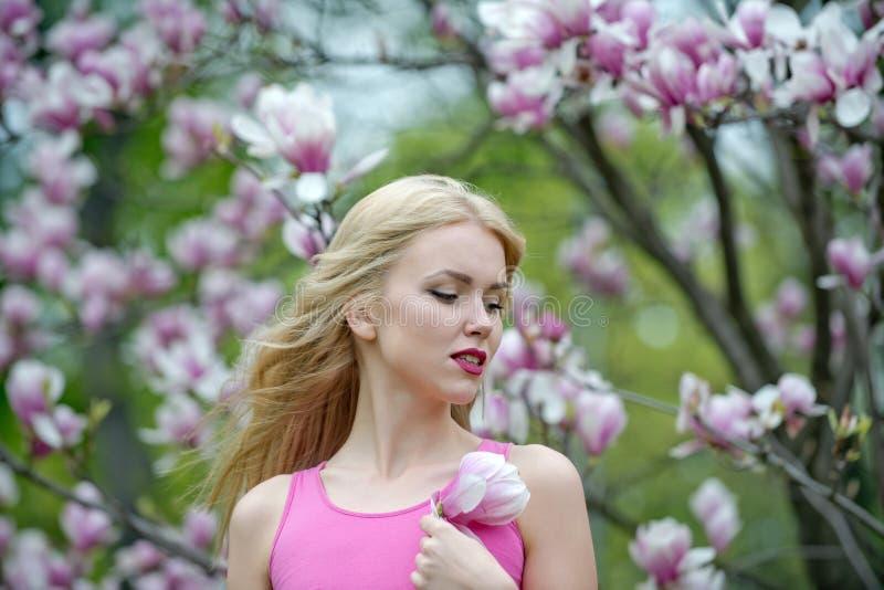 Пасха, смешная женщина в стеклах и ушах зайчика на цветке магнолии весны стоковые изображения