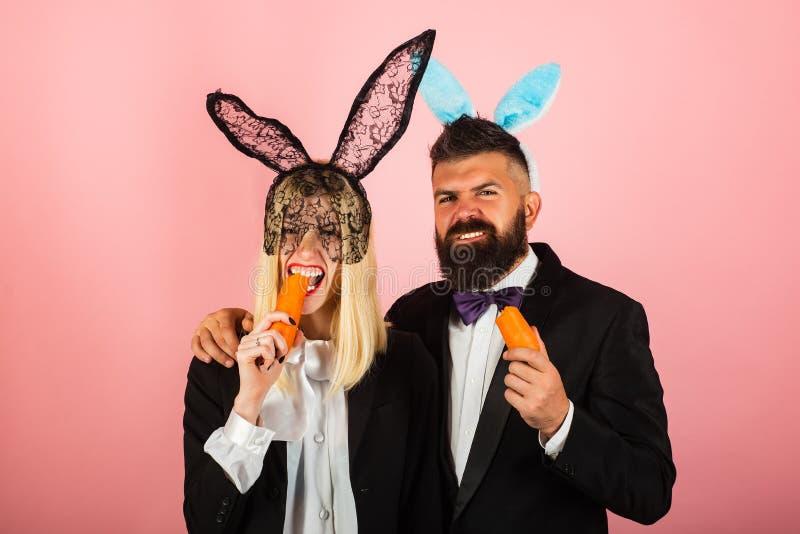 пасха смешная Милые пары кролика зайчика Платье зайчика пасхи Счастливые пары пасхального яйца едят морковь стоковое фото rf