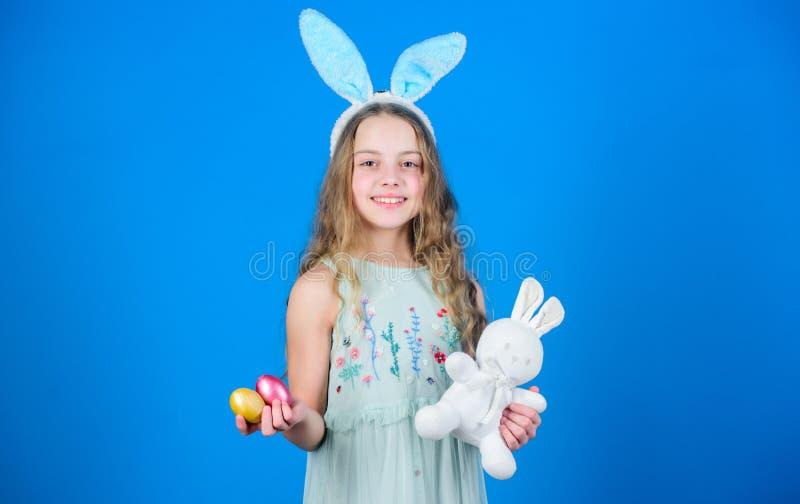 пасха счастливая Счастливая маленькая девочка нося уши зайчика пасхи Небольшая девушка в держателе зайчика держа покрашенные яйца стоковая фотография rf
