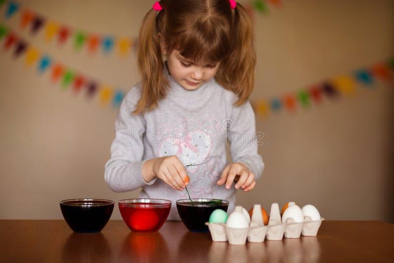 пасха счастливая Художник маленькой девочки покрасил яйца Ребенк подготавливая для пасхи покрашенная рука Краска пальца Концепция стоковая фотография rf