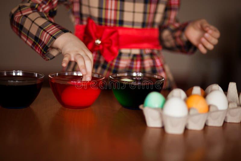 пасха счастливая Художник маленькой девочки покрасил яйца Ребенк подготавливая для пасхи покрашенная рука Краска пальца Концепция стоковые изображения